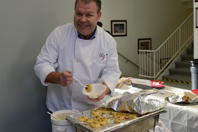 "Robert ""RJ"" Johnson, Joint Force Headquarters-National Capital Region/U.S. Army Military District of Washington J4 logistics senior supply management officer, displays his first placing winning dish called the Pinwheel Regatta, during a bake off competition fundraiser for the 2014 JFHQ-NCR/MDW Organizational Day at Fort Lesley J. McNair, April 17, 2014."