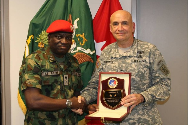 MG Pat Akem, the Nigerian Provost Marshal General, presents MG Quantock, Provost Marshal General with a plaque during a recent office visit.