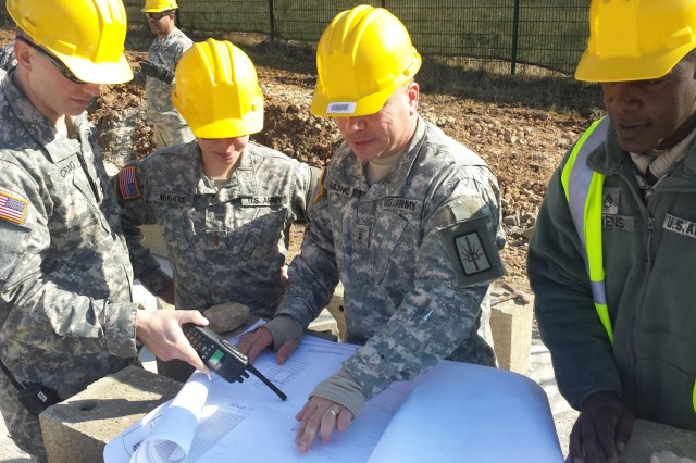 New York Army National Guard Chief Warrant Officer Michael Quijano, 1156th Engineer Company (center) reviews architectural plans with Staff Sgt. Aaron Owens (right), 2nd Lt. Noelle Makhoul (center left) and Sgt. 1st Class John Craig (left) during the construction of a multi-use building at the Joint Multinational Readiness Center, Hohenfels, Germany, in March. Along with their other accomplishments, company troops and two New York Air National Guardsmen constructed two multi-use buildings, complete with wiring, at the center during a three-week period. Quijano is from Staten Island, N.Y., Owens is from Poughkeepsie, N.Y., Makhoul is from Fort Lee, N.J., and Craig is from Tillson, N.Y. (Photo by Capt. Dan Colomb, 1156th Engineer Company)