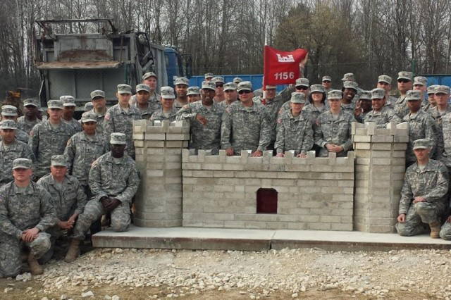 New York National Guard engineer troops pose with the brick castle they built to commemorate their construction of two multi-use buildings at the Joint Multinational Readiness Center, Hohenfels, Germany, in March. The castle represents the Army engineer branch. Along with their other accomplishments, troops of the 1156th Engineer Company and two New York Air National Guardsmen inventoried, reorganized and cleaned a construction supply yard, and conducted driver training at the center during a three-week period. (Photo by Capt. Dan Colomb, 1156th Engineer Company)