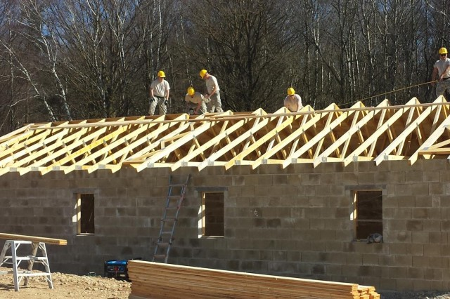 New York Army National Guard engineer troops install roof trusses on a building at the Joint Multinational Readiness Center, Hohenfels, Germany, in March. Along with their other accomplishments, 1156th Engineer Company troops and two New York Air National Guardsmen constructed two multi-use buildings, complete with wiring, at the center during a three-week period. (Photo by Capt. Dan Colomb, 1156th Engineer Company)