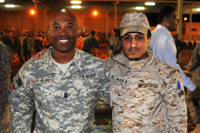 Command Sgt. Maj. Dennis Bellinger, senior enlisted leader, 1st Battalion, 67th Armor Regiment, 2nd Armored Brigade Combat Team, 4th Infantry Division, poses with a Soldier of the Royal Saudi Land Forces after switching name tags following a cultural event and dinner at the Tactical Training Center, Tabuk, Saudi Arabia, April 5, 2014. The dinner was part of the opening ceremony for Friendship and Ironhawk 3, a two-week military-to-military exercise focused on strengthening stability and improving interoperability between the two nations.