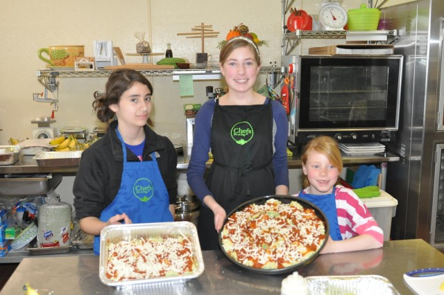 Angelica Kadan, 12, (left), daughter of Staff Sgt. Adli Kadan who is deployed to Afghanistan, Melanie Albers, 14, (center), and Katherine Albers, 7, (right), daughters of Lt. Col. Greg Nordyke, 416th Theater Engineer Command personnel mobilizations officer, show their lasagna creation during an event that that taught them the process for building ingredients for making a healthy meal as part of an event that recognizes and shows appreciation for military children during the Month of the Military Child celebrating their service for the challenges they face.