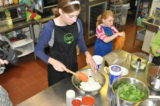Melanie Albers, 14, daughter of Lt. Col. Greg Nordyke, 416th Theater Engineer Command personnel mobilizations officer, learns the process to making lasagna and preparing a meal during an event that recognizes and shows appreciation for military children during the Month of the Military Child celebrating their service for the challenges they face.