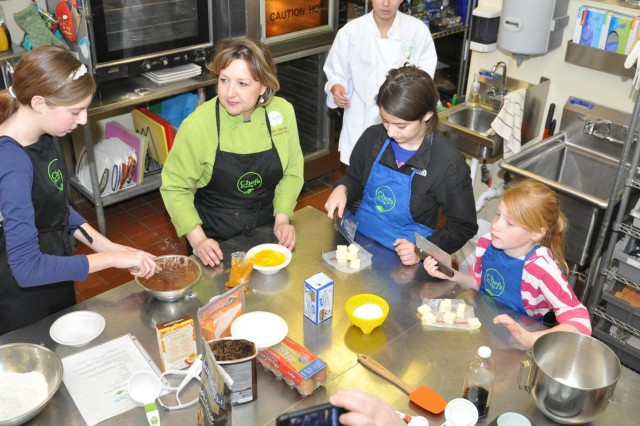 Melanie Albers, 14, (left), Angelica Kadan, 12, (center right), Katherine Albers, 7, (far right) learn to measure ingredients for making cupcakes with Laura Valco, Chefs for a Day owner, (center left) during an event that recognizes and shows appreciation for military children during the Month of the Military Child celebrating their service for the challenges they face.
