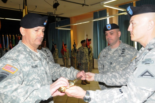 Col. John G. Norris, Joint Multinational Readiness Center commander, (right) passes the ceremonial noncommissioned officer sword to incoming JMRC command sergeant major, Command Sgt. Maj. Nicholas A. Rolling (left) while Command Sgt. Maj. Eric C. Dostie looks on.