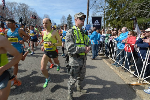 Tech. Sgt. Gary Bent, 102nd Security Forces Squadron, 102nd Intelligence Wing, Massachusetts Air National Guard, scans the near side of the crowd during the start of the mobility impaired runners of the 2014 Boston Marathon, April 21, 2014. Approximately 600 Massachusetts National Guardsmen are deployed along the route to assist local authorities in ensuring that the 2014 Boston Marathon is as safe as realistically possible. Due to the record number of runners this year, Guardsmen from numerous states are augmenting the Massachusetts National Guard's own specialized units.
