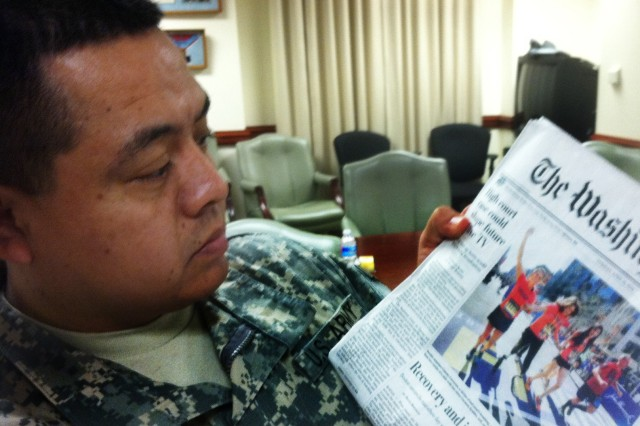 Staff Sgt. Julio Larrea gazes at a front-page newspaper photo April 22, 2014, showing a family crossing the finish line of this year's Boston Marathon, held a day before.