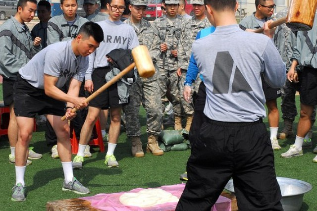 Bundang, Kyungido native, Pfc.  Hong, Myoungwon, an automated logistics specialist assigned to Troop E, 4th Attack Reconnaissance Squadron, 6th Calvary Regiment, pounds rice with a mallard, demonstrating how to make traditional Korean rice cakes during KATUSA-U.S. Friendship Week, April 17,  on Camp Humphreys, South Korea. United States Army Garrison Humphreys hosted KUSFW to promote friendship and cross-cultural understanding between Soldiers. (Photo Courtesy of United States Army Garrison Public Affairs)