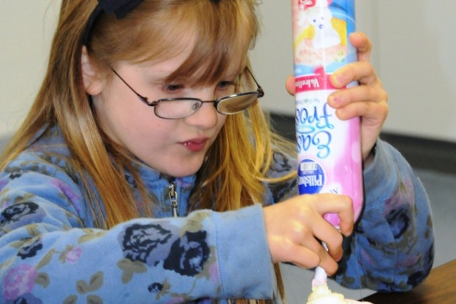 Priscilla Whorton decorates her own cupcake during Job Shadow Day at Hohenfels Elementary School, recently.