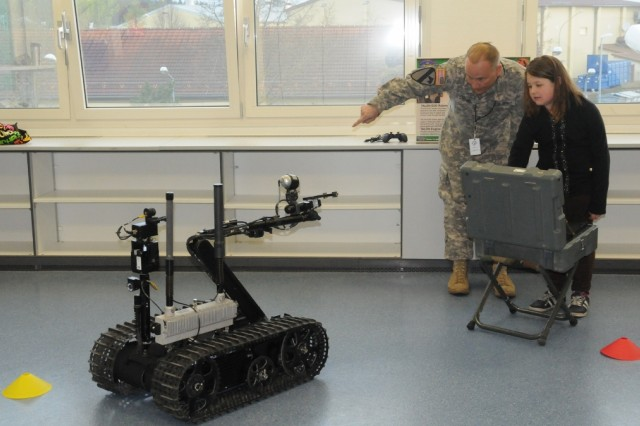 A student pilots a robot under the direction of Chief Warrant Officer 3 Mike Ebinal during Job Shadow Day at Hohenfels Elementary School, recently.