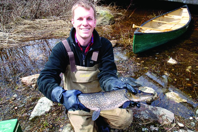 Chris Whitman poses with a large northern pike he caught on Indian River. Whitman is an intern with the Fish and Wildlife Branch.
