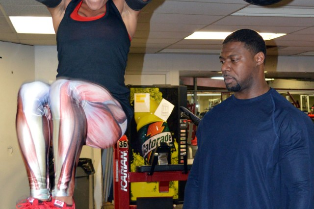 Under the watchful eye of her personal trainer and mentor, Staff Sgt. Michelle Larrieux trains for bodybuilding competitions.
