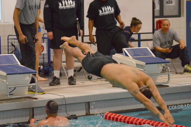 Sgt. 1st Class Jason Keller, first sergeant, Company A, Warrior Transition Battalion, dives into the pool as Staff Sgt. Eric Faulkner finishes his lap during a 200-meter relay race, April 16, 2014. The race was part of the Warrior Transition Battalion Commander's Stakes games at the Olympic Training Center in Colorado Springs, Colo.