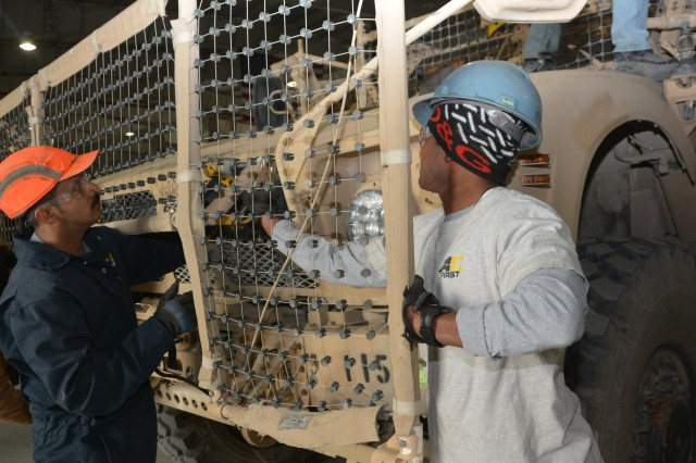 AC-First workers remove RPG netting from a MRAP All-terrain vehicle Apr. 18. Vehicles turned in to the Logistics Task Force Bagram, Redistribution Property Assistance Team have government furnished equipment and other added-on equipment removed as one of the first steps in processing a vehicle in the RPAT yard.