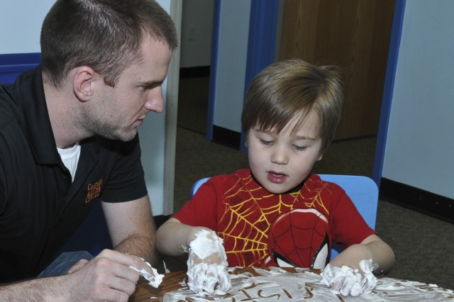 """COLORADO SPRINGS, Colo. -- Pete Libby, left, lead behavioral clinician, Colorado Autism Center, helps Tristram Waller, 4, son of Staff Sgt. Billy Waller, who is currently deployed to Afghanistan with the 4th Infantry Brigade Combat Team, 4th Infantry Division, write his name in shaving cream at the Colorado Autism Center in Colorado Springs April 10, 2014. """"A lot of children with autism have sensory issues and do not like the feel of different textures,"""" Libby said. """"The point of the exercise with the shaving cream helps them get over that dislike; it exposes them to something they may encounter in an everyday living environment."""""""