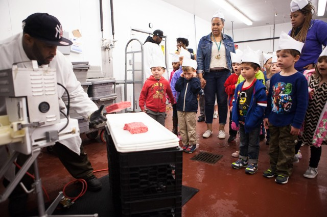 Damian Lofton, work leader, shows children from Cody Child Development Center's Robins B class how ground beef is made during a tour of Joint Base Myer-Henderson Hall's commissary April 22, 2014. The children toured the commissary as a part of Earth Day activities.