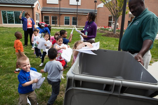 Children from the Cody Child Development Center throw paper into a recycle bin during Earth Day April 22, 2014. The paper was then shredded and sent to be recycled.