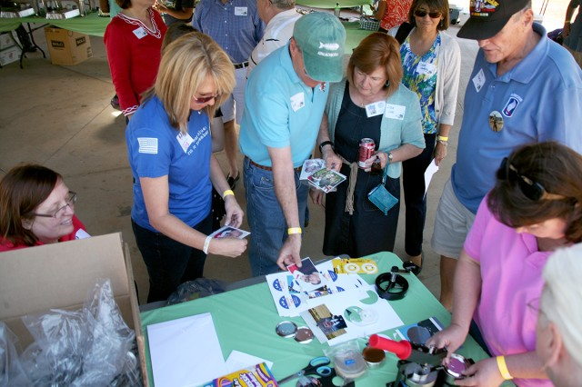 Kerrie Branson, Survivor Outreach Services coordinator, standing left, helps surviving family members make buttons from photographs of their fallen Soldier during the SOS Spring Fling April 26 at the Huntsville Botanical Gardens. The event was sponsored by the U.S. Army Space and Missile Defense Command/Army Forces Strategic Command.