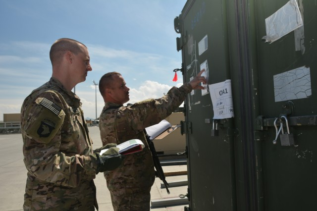 """Capt. David E. McCormick, with Logistics Task Force Bagram, flight line officer-in-charge, and Sgt. 1st  Class Ivan K. Line, Logistics Task Force Bagram flight line non-commissioned officer-in-charge, conduct one of two daily inventories of equipment staged at the cargo ramp on Bagram Airfield, Afghanistan. Equipment awaiting movement by the U.S. Air Force is inventoried twice daily and is ready for scheduled and """"opportune air"""" flights."""