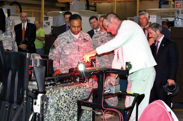 Gen. Dennis L. Via, commanding general of the U.S. Army Materiel Command, listens as T.J. LaPointe, a project lead with the PIF of the U.S. Army Aviation and Missile Research, Development and Engineering Center (AMRDEC), briefs mission equipment projects, including the Apache infrared (IR) strobe and Federal Aviation Administration strobe and position light at Redstone Arsenal, Ala., in November 2013. Used with existing night vision goggles, the PIF IR strobe provides pilots a way to distinguish Army aircraft at night without being identified by the enemy.