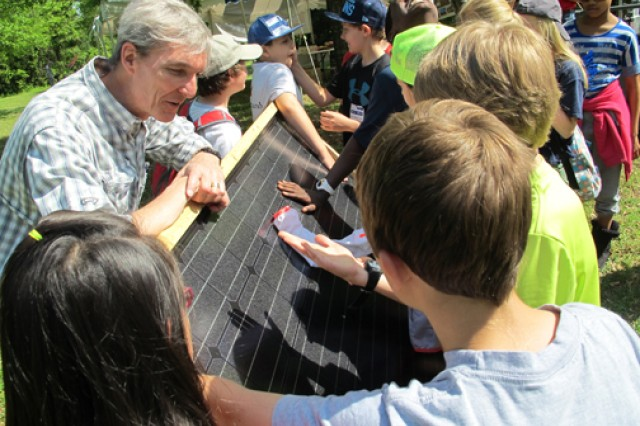 Jeff Waters, an instructor at Calhoun Community College's Clean Energy Center, explains solar technology using a solar panel, April 24, 2014, during  the Earth Day event at the Redstone Arsenal, Ala., Path to Nature. The students are from Horizon Elementary School.