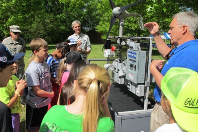 Jerry Adams, an instructor at Calhoun Community College's Clean Energy Center, explains windmill technology using a wind turbine trainer, April 24, 2014, during the Earth Day event at the Redstone Arsenal, Ala., Path to Nature. The students are from Horizon Elementary School.