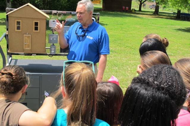 Jerry Adams, an instructor at Calhoun Community College's Clean Energy Center, explains energy conservation using a energy auditing  trainer (model house) April 24, 2014 during the Earth Day event at the Redstone Arsenal, Ala., Path to Nature. The students are from Monte Sano Elementary School.