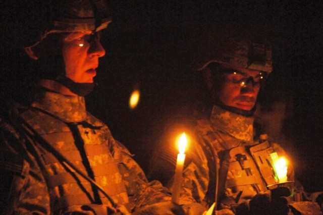 YARMOUK, Iraq-- Chaplain (Capt.) Troy Parson, 2nd Battalion, 32nd Field Artillery, attached to 2nd Brigade Combat Team, 101st Airborne Division (Air Assault), leads Soldiers in a prayer at a candlelight ceremony at Joint Security Station Torch in Yarmouk, Iraq, Dec. 25, 2007.