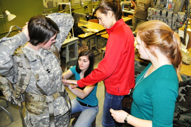 Worcester Polytechnic Institute student Marlisa Overton (far left) test fits the female friendly rucksack hip belt design as fellow students Erin LaRoche, Amy Babeu and Rachel Matty (left to right) note the position of the pads.
