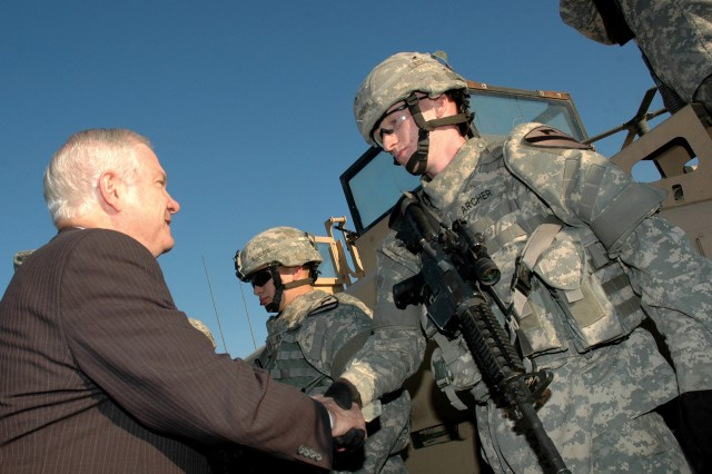 Then-Secretary of Defense Robert Gates greets Pfc. Dylan Archer, an infantryman with the 2nd Brigade, 1st Cavalry Division, outside the division's deployed headquarters at Camp Liberty, Iraq, in December 2006.