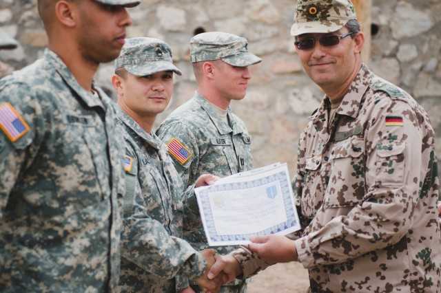 Lt. Col. Nils Wetzel, deputy commander for the German Air Defense Center at Fort Bliss, Texas, presents a certificate to Sgt. 1st Class Richard Lacy, of U.S. Army Operation Test Command, for his participation in the German Armed Forces Military Proficiency test. The test took place throughout Fort Bliss March 7 -- 14, 2014.