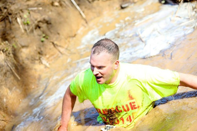 RescueRun2: Maj. Jade Miller, Army Contracting Command-Rock Island contract specialist, makes his way through a muddy pit obstacle, one of more than 20 obstacles that challenged runners at this year's Rescue Run, held in Aledo, Ill., on April 19. Miller and two other ACC-RI employees, Contracting Officer Tracey DuBord and Contract Specialist Matthew Ward, took part in this year's event.