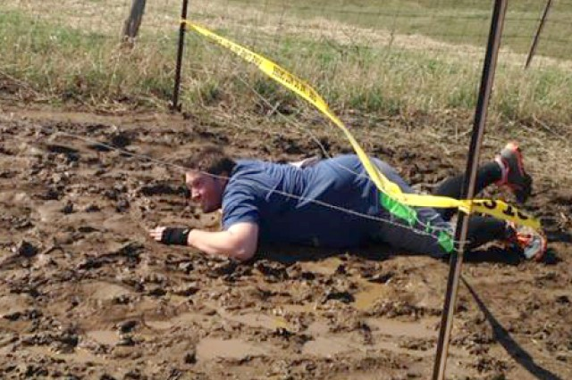 Matthew Ward, Army Contracting Command-Rock Island contract specialist, crawls in mud under a chicken wire obstacle during this year's Rescue Run in Aledo, Ill., on April 19. Ward and two other ACC-RI employees, Contracting Officer Tracey DuBord and Contract Specialist Maj. Jade Miller, took part in this year's event.