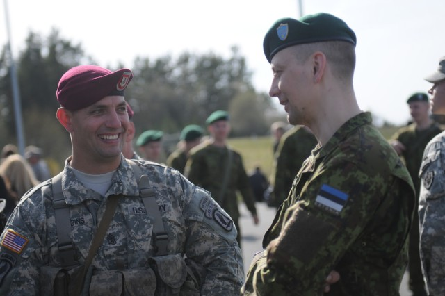 First Sgt. Benjamin Loggins, with Chosen Company, 1st Battalion, 503rd Infantry Regiment, 173rd Airborne Brigade, converses with an Estonian soldier after a ceremony commemorating new land forces exercises, April 28, 2014. The paratroopers, who are part of a company-sized contingent, arrived to begin exercises with Estonian troops in a series of expanded U.S. land forces training activities in Poland and the Baltic region scheduled to take place for the next few months and beyond. The multinational training fulfills the USAREUR strategic objective of preserving and enhancing NATO interoperability and demonstrates the United States' commitment to NATO Allies.