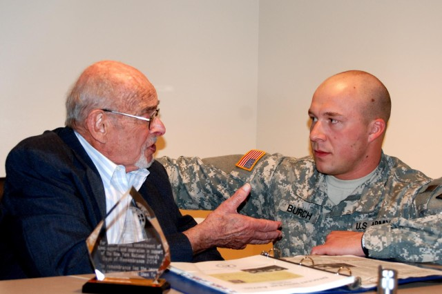 "Holocaust survivor Martin Becker, 87, speaks to New York Army National Guard Sgt. Christopher Burch assigned to the 42nd Combat Aviation Brigade, following a discussion about his experiences growing up in Germany and escaping Nazi rule during 1939, April 30. The presentation is in observance of Holocaust Remembrance week, April 27-May 4, 2014. The talk focused on a book written by Bruce Chadderton of Auckland, New Zealand, titled ""Descent into the Abyss: The Shoah"" published in 2012 by the Education Fund, Society of Israel Philatelist, which was dedicated to Becker's sister, brother-in-law and niece, all murdered during the Holocaust."