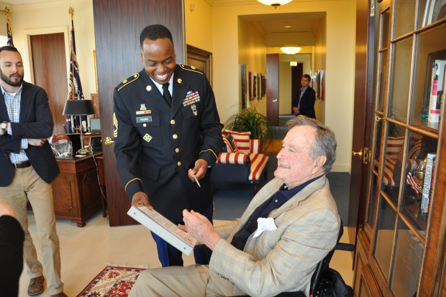 Former President George H.W. Bush (right) and Army Reserve Master Sgt. Branden Young (left) share a moment after Bush signed as the witness to Young's military re-enlistment contract in Houston, Texas, Friday, April 25, 2014. Young, a Virginia reservist, successfully requested Bush as the official to preside over the ceremony. Young and others traveled to Bush's post-presidential office for the event.