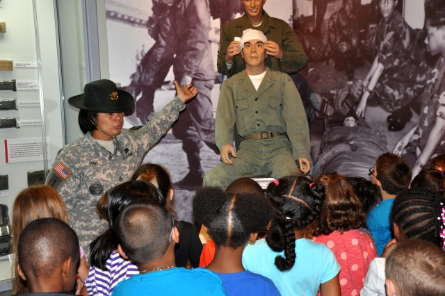 Staff Sgt. Margaret Louis, a drill sergeant with 3rd Battalion, 13th Infantry Regiment, explains first aid to Fort Jackson students April 25, 2014 at the Basic Combat Training Museum. The students visited the museum as part of the installation's Month of the Military Child activities.
