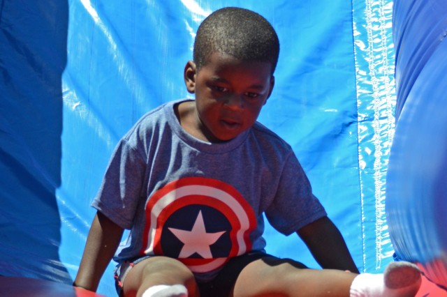 Josiah Kirksey, 3, uses one of several bounce houses during Fort Jackson's Month of the Military Child Family Fun Fair, April 26, 2014, at Patriot Park.