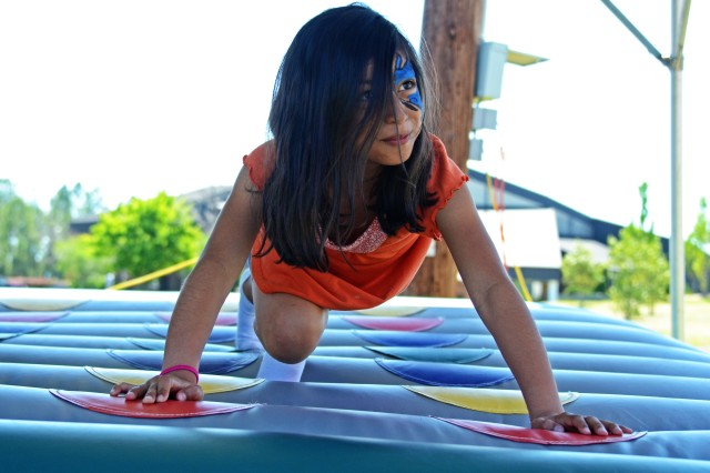 Alyssa Guerrero, 10, plays Twister during Fort Jackson's Month of the Military Child Family Fun Fair at Patriot Park, April 26, 2014. The fair offered free rides, games and activities to military children. It capped off this year's Month of the Military Child events.