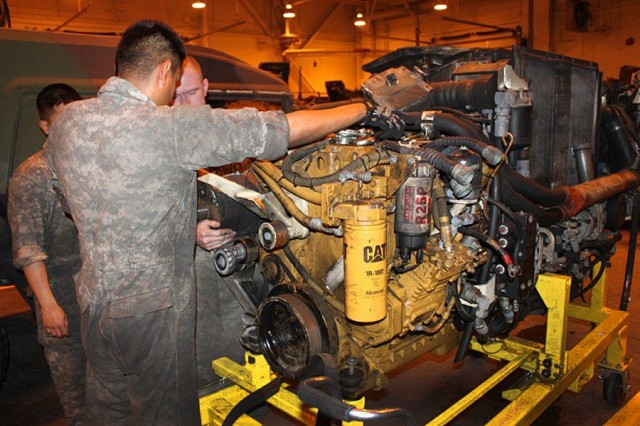 Pfc. Jeremiah Balete, Spc. Zavier Lorettor, and Pfc. Gregory Bettencourt, 25th Brigade Support Battalion, 1st Stryker Brigade Combat Team, 25th Infantry Division, at Fort Wainwright, Alaska, repair full up power packs instead of replacing them, saving the unit more than $200,000 on each pack repaired.