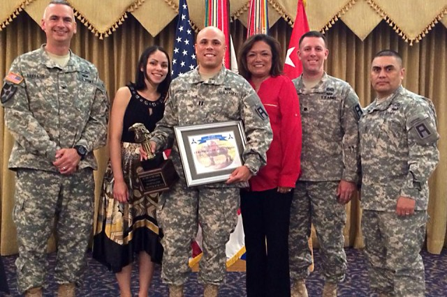 From left to right, Col. John Leffers, 479th Field Artillery Brigade commander; Tiffany Brown and her husband Capt. William Brown, of Headquarters and Headquarters Company, 2nd Battalion, 3rd Regiment, 479th Field Artillery Brigade; Sylvia Phipps wife of Maj. Gen. Warren E. Phipps Jr., Division West commander; Lt. Col. Scott Ward, commander of 2nd Battalion, 381st Regiment, 479th Field Artillery Brigade; and DIVWEST Command Sgt. Maj. Patrick K. Akuna Jr., pose for a photo as Brown earns distinction as First Army Division West's 2013 Volunteer of the Year during ceremonies at Club Hood April 23, 2014.