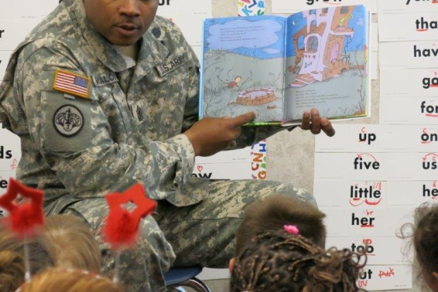 "FORT CARSON, Colo. -- 1st Sgt. Ed Malone, Blackfoot Troop, 2nd Squadron, 1st Cavalry Regiment, 1st Stryker Brigade Combat Team, 4th Infantry Division, reads ""The Lorax"" to first grade students at Weikel Elementary School, April 22."