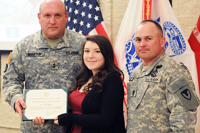 Maj. Gen. John Wharton, commanding general of Army Sustainment Command, and his senior enlisted adviser, Command Sgt. Maj. James Spencer, present Cassie Berta with a certificate of appreciation for singing the national anthem during the Days of Remembrance ceremony in Heritage Hall at Rock Island Arsenal, April 29. Cassie Berta is the granddaughter of keynote speaker, Jeno Laszlo Berta, a witness to the Holocaust. (Photo by Sgt. 1st Class Shannon Wright, ASC Public Affairs)