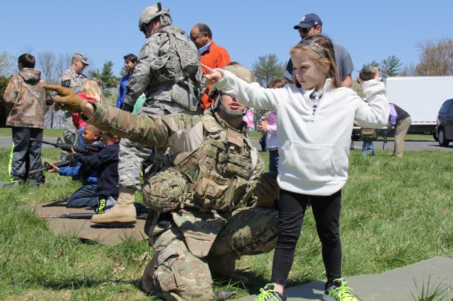 Haley Belcher learns correct form to throw a replica hand grenade at a target during the Bring Your Daughters and Sons to Work Day event April 24 at the Army's Test and Evaluation Command at Aberdeen Proving Ground, Md. This activity helped children recognize the way Soldiers train.