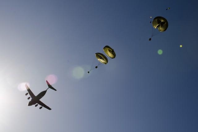 Parachute-rigged containerized supplies are seen being dropped by a C-17 aircraft high above Adazi Drop Zone, Latvia, May 2, 2014, as paratroopers from the 173rd Airborne Brigadeconduct an aerial resupply mission.