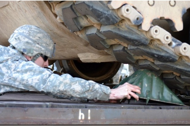 A Soldier from the 16th Sustainment Brigade, 21st Theater Sustainment Command, carefully places a block in place for a tracked recovery vehicle during railhead training at Quartermaster Kaserne in Baumholder, Germany, April 10, 2014.