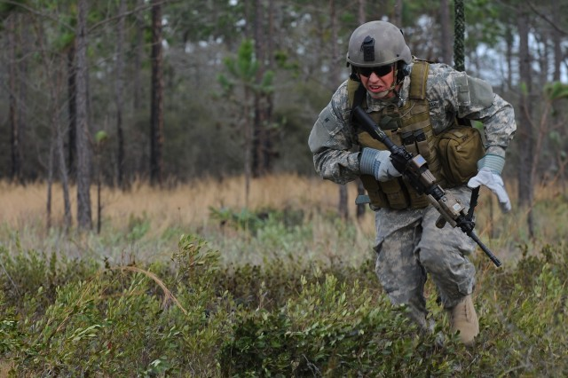 A Special Forces Soldier advances during Exercise Emerald Warrior 2011, at Hurlburt Field, Florida. The Soldier is wearing a Modular Integrated Communications Helmet with a tactical communications headset. The assault vest, worn over an ACU uniform, features a First Aid Kit pouch attached on the left side and spare pistol magazines on the front-left. Note the fast-rope gloves worn by this Special Forces operator. His M4A1 carbine is fitted with a SU-231 sight and AN/PEQ-15 Target Pointer/Illuminator/Aiming Light.