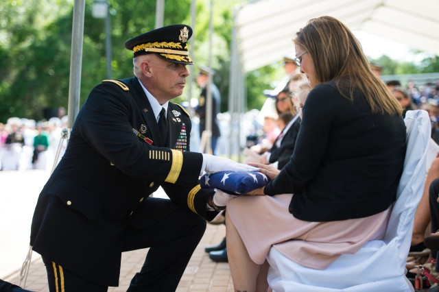 "20th CBRNE Command Commander Brig. Gen. J.B. Burton presents wife of Fallen Soldier Staff Sgt. Kenneth ""Wade"" Bennett with a U.S. Flag that was flown over the Explosive Ordnance Memorial (EOD) at the EOD 45th Annual <emorial Service at the Kauffman EOD Training Complex on Eglin Air Force Base, FL, May 3, 2014.  The Service is held every year to honor EOD Technicians who had sacrificed their lives in the performance of duty.  (U.S. Army photo by Staff Sgt. Steve Cortez/ Released)"