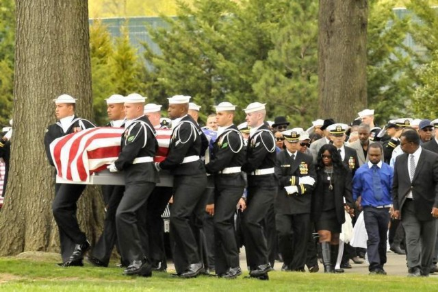 The family of U.S. Navy Petty Officer 2nd Class Mark A. Mayo (right) follows his flag draped casket to his eventual gravesite at Arlington National Cemetery April 25.